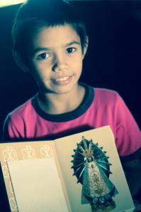 Tobias from the barrio with an image of the Virgin of Caacupe.